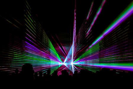 Buntes Laser-Show-Nachtleben-Vereinstadium mit Parteileutemenge. Luxusunterhaltung mit Publikumssilhouetten in Nachtclubveranstaltung, Festival oder Silvester. Lichtstrahlen und Strahlen leuchten bunt.