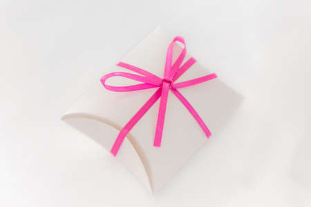 Surprise cute valuable luxury gift with loop on white table.
