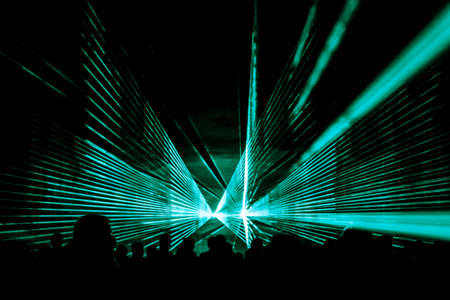Turquoise laser show nightlife club stage and party people crowd. Luxury entertainment with audience silhouettes in nightclub event, festival or New Years Eve. Beams and rays shining colorful lights.
