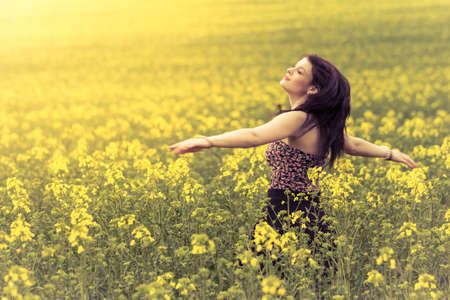 Beautiful woman in meadow of yellow twist from behind. Attractive authentic young girl enjoying the luxury of warm summer sun sunshine and wellbeing youth in wide landscape. Part of series.