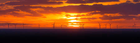 Panorama sunset sun at windmills offshore clean wind power farm. Many energy stations on sea water, clouds in the sky. Sustainable regenerative renewable industry business preventing climate change.