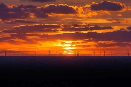 Sunset at wind turbines windmills offshore clean power farm far. Many energy stations on sea water, clouds in the sky. Sustainable regenerative renewable industry business preventing climate change. Reklamní fotografie