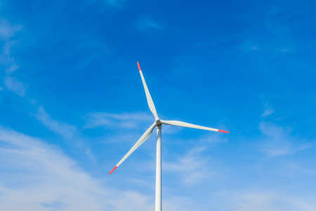 Rotating windmill generating renewable energy with wind power. Sustainability by windmills turbines preventing climate change with regenerative clean green nature energy. Windy blue sky with clouds Reklamní fotografie