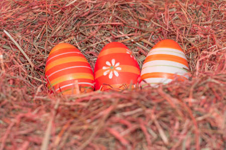 Easternest basket tradition red hidden easter eggs to search. Traditional easter holiday festival celebration with three reddish eggs in hay straw in warm spring colors. Beautiful present symbol. Foto de archivo - 99989882