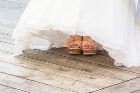 Wedding bride shoes and feet under white bridal gown tulle. The woman is wearing luxury lifestyle bridal dress. The girl is showing her feet with white shoes and pink nail varnish. Wooden floor.