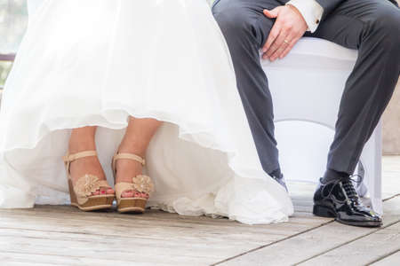 Wedding bride and groom sitting next each other at marriage. The man and the woman wearing luxury bridal dress, suit and shoes. The girl shows her feet with nail varnish. Male shoe is polished. 스톡 콘텐츠