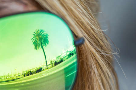 Single tropical luxury paradise beach palm glasses reflection. Exciting mirror imaging at sunglasses on head. Beautiful symbol of tourism vacation trip travelling to holiday dream island. Copypace.
