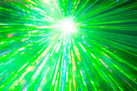 Green laser show rays at top nightlife party event performance. Luxury entertainment with bright light source and many beams and streams to every side at nightclub event, festival or New Years Eve.