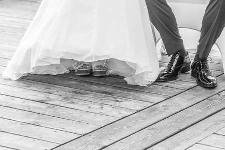 Wedding bride and groom sitting next each other at marriage. The man and the woman wearing luxury bridal dress, suit and shoes. The girl shows her feet with nail varnish. Male shoe is polished. 写真素材