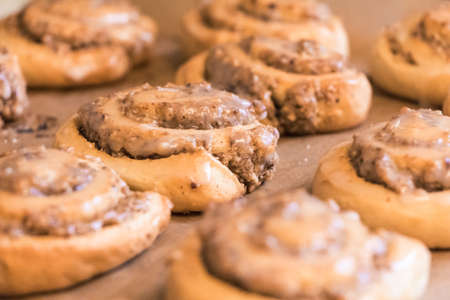 Tasty cinnamon rolls pastry with sugar frosting nuts stuffing. Delicious leavened dough pastries for breakfast, dessert or brunch. Yummy juicy backed traditional goods from bakery or confectionery. 写真素材