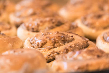Tasty cinnamon rolls pastry with sugar frosting nuts stuffing. Delicious leavened dough pastries for breakfast, dessert or brunch. Yummy juicy backed traditional goods from bakery or confectionery. Foto de archivo - 104958703