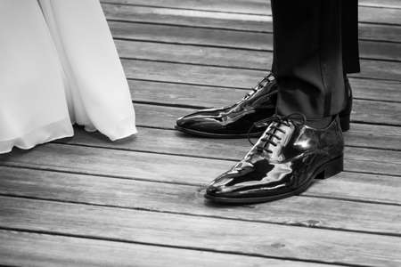 Wedding bride and groom standing next each other at marriage. The man and the woman wearing luxury lifestyle bridal dress, suit and shoes. The Male shoe luster is polished. Wooden floor copyspace.