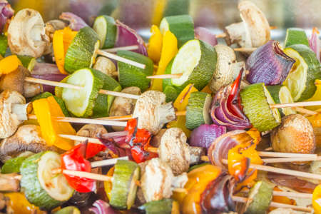 Delicious vegetable skewer food grilled at summer barbecue. Fresh light juicy vegetables skewers with zucchini onion pepper mushrooms for estival low calorie bbq. Colorful healthy appetizer or supplement.
