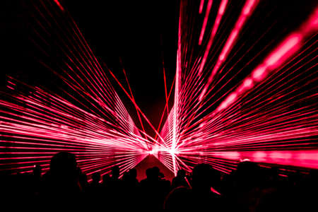 Red laser show nightlife club stage with party people crowd. Luxury entertainment with audience silhouettes in nightclub event, festival or New Years Eve. Beams and rays shining colorful lights.