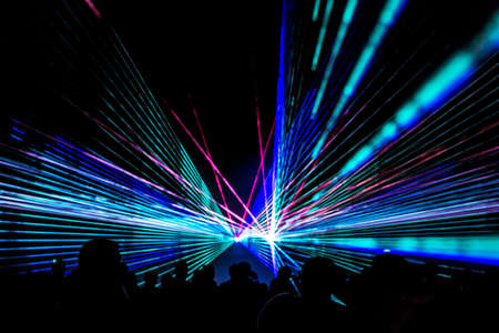 Colorful laser show nightlife club stage with party people crowd. Luxury entertainment with audience silhouettes in nightclub event, festival or New Years Eve. Beams and rays shining colorful lights.