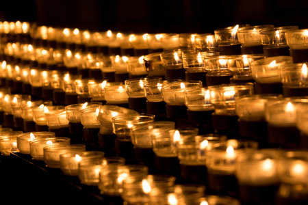 Group of grief candles in church for faith resurrection obituary. Candle is symbol of sacrifice for peace hope strength of life and soul. Also power towards sorrows and pain together in parish service Foto de archivo - 105350348