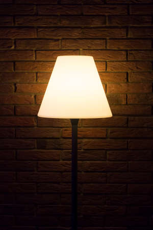 Old vintage evening lamp shines bright light to dark wall. Reading lamp for bedtime stories at night. Also a visual for thinking barrier problems or diseases like depressions or dementia. Foto de archivo - 107139683