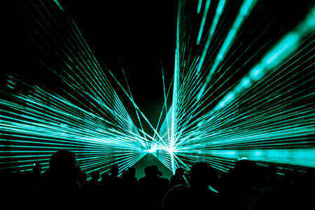 Turquoise laser show nightlife club stage at party people crowd. Luxury entertainment with audience silhouettes in nightclub event, festival or New Year's Eve. Beams and rays shining colorful lights. Foto de archivo - 107139686