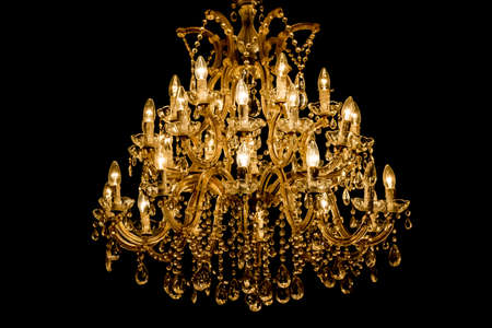 Luxury interior chandelier has light candles and dark background. Noble candelabra hanging on ceiling with lots of little gems. Premium decoration for palace gala, villa business meeting or wedding. Foto de archivo - 107139689