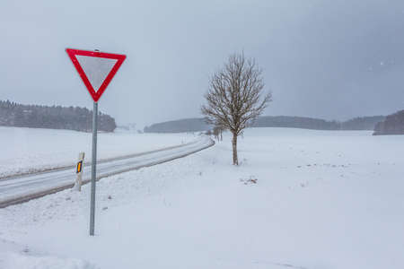 White empty snowy icy winter road track with yield sign. The street track is slick and frozen. Foto de archivo - 126009857