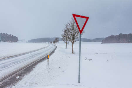 White empty snowy icy winter road track with yield sign. The street track is slick and frozen. 写真素材