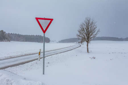 White empty snowy icy winter road track with yield sign. The street track is slick and frozen. High dangerous risk of an accident through the blizzard snowstorm and severe weather at christmas time season. 免版税图像 - 131619173