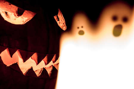 Carved spooky halloween pumpkin and scary mystery fire ghosts. Big helloween autumn symbol with mad face, glowing eyes, mouth and teeth. Scary hot nightmare horror with evil smile at october 31st.