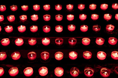 Group of red candles in church for faith resurrection prayer. Candlelight fire flames in rows are silent religion symbol for peace, life and soul. Obituary hope sacrifice against sorrows and pain.