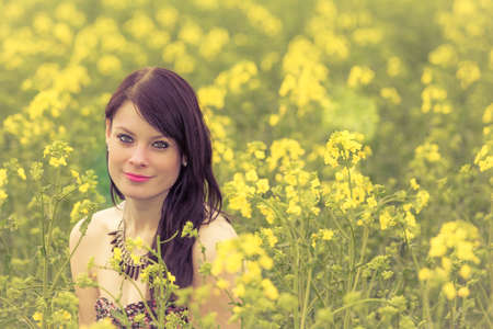 Smiling summer love woman sitting down in rapeseed field happy. Attractive young beauty girl enjoying the warm sunny sun in nature takes time feeling sustainability contemplation and youth wellbeing Archivio Fotografico
