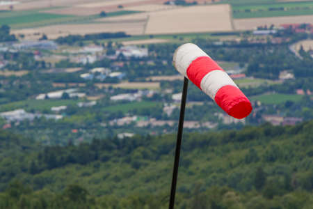 Red and white windsock measuring stormy windy weather at hill. Meteorology measurement instrument show wind force at hurricane. Forecast of dangerous storm intensity for cyclone or high in nature. Stock Photo