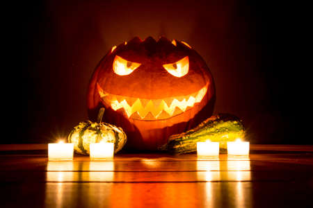 Spooky carved halloween pumpkin with candles and small pumpkins. Big helloween autumn symbol with mad face, glowing eyes, mouth and teeth. Scary hot nightmare horror with evil smile at october 31st.