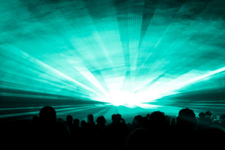 Turquoise laser show nightlife club stage at party people crowd. Luxury entertainment with audience silhouettes in nightclub event, festival or New Years Eve. Beams and rays shining colorful lights.