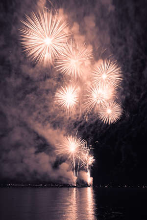 Luxury fireworks event sky water sea show with golden stars. Premium entertainment magic star firework at e.g. New Years Eve or Independence Day party celebration. Nice lake surface reflections.