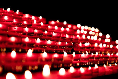 Group of red candles in church for faith resurrection prayer. Candlelight fire flames in rows are silent religion symbol for peace, life and soul. Obituary hope sacrifice against sorrows and pain. Stockfoto