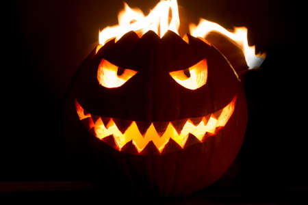 Carved spooky halloween pumpkin with glowing hot fire flame head. Big helloween autumn symbol with mad face, glowing eyes, mouth and teeth. Scary hot nightmare horror with evil smile at october 31st.