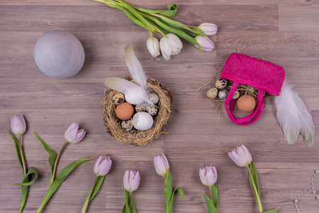 Easter holiday decoration design with eggs feathers bag tulips. Beautiful decoration easternest with egg flowers and basket for traditional celebration in april. Handmade fun tinker luxury bouquet.