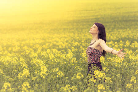 Happy beautiful woman in free summer love of youth wellbeing. Attractive young beauty girl enjoying the warm sunny sun in nature rapeseed field takes time feeling sustainability and contemplation.