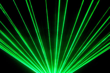 Green laser show nightlife club stage and shining sparkling rays. Luxury entertainment in nightclub event, festival, concert or New Years Eve. Ray beams are symbol for science and universe research.