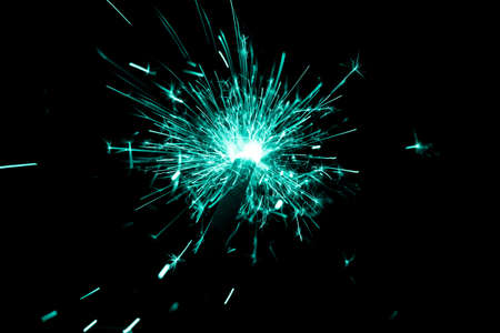 Turquoise sparkler countdown on fire with spread glitter sparks. Luxury entertainment at eg New Years Eve, Independence Day or birthday party celebration. Glowing light spark on dark background. Banco de Imagens