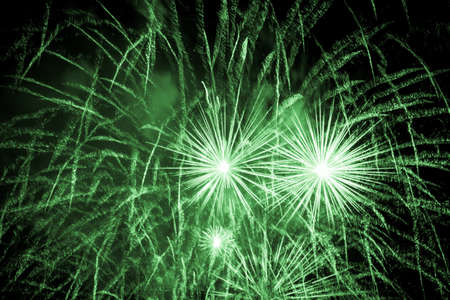 Luxury fireworks event sky show with green big bang stars. Premium entertainment magic star firework at eg New Years Eve or Independence Day party celebration. Black dark night background.