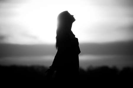 Youth woman soul at white sun meditation awaiting future times. Silhouette in front of sunset or sunrise in summer nature. Symbol for healing burnout therapy, wellness relaxation or resurrection. Stok Fotoğraf