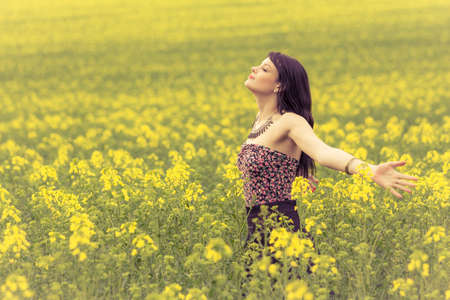 Happy beautiful woman in free summer love of youth wellbeing. Attractive young beauty girl enjoying the warm sunny sun in nature rapeseed field takes time feeling sustainability and contemplation. Banque d'images