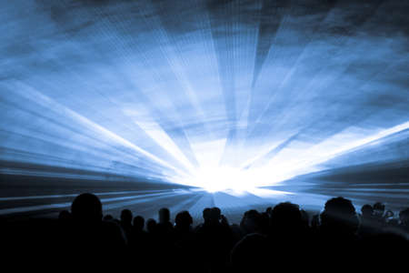Blue laser show nightlife club stage with party people crowd. Luxury entertainment with audience silhouettes in nightclub event, festival or New Years Eve. Beams and rays shining colorful lights.