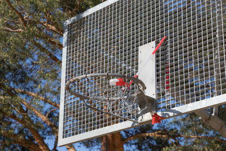 Corona virus quarantine lockdown of playground basketball basket. Closure by barrier tape. Covid-19 safety prevention action containing pandemic spread risk. Corona virus restriction by law regulations 免版税图像