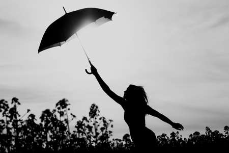 Unplugged free silhouette woman umbrella up to black white sky. Nature girl at windy rainy day has adventure wanderlust. Wonderful scene of imagination power and departure to new horizons in youth.