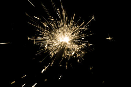 Yellow sparkler countdown on fire with spread of glitter sparks. Luxury entertainment at eg New Years Eve, Independence Day or birthday party celebration. Glowing light spark on dark background.
