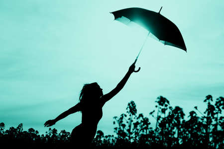 Unplugged free silhouette woman has umbrella up to turquoise sky. Nature girl at windy rainy day has adventure wanderlust. Wonderful scene of imagination power and departure to new horizons in youth.