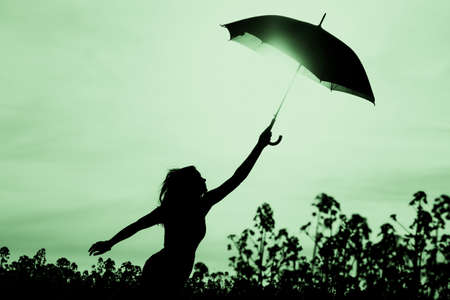 Unplugged free silhouette woman with umbrella up to green sky. Nature girl at windy rainy day has adventure wanderlust. Wonderful scene of imagination power and departure to new horizons in youth.