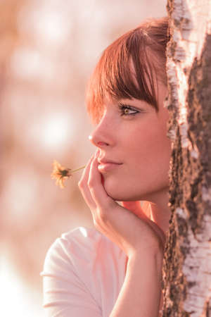 Beautiful girl with flower dreaming in nature at tree trunk. Young carefree woman with best health at sunny summer day in youth time. Perfect skin with authentic natural beauty cosmetic makeup.