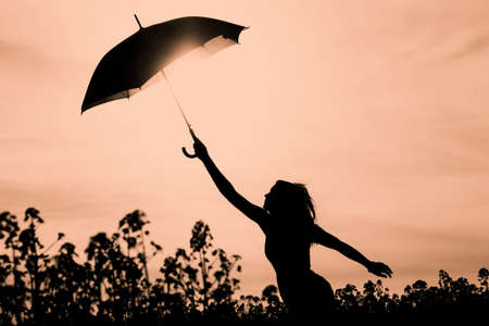 Unplugged free silhouette woman with umbrella up to orange sky. Nature girl at windy rainy day has adventure wanderlust. Wonderful scene of imagination power and departure to new horizons in youth.